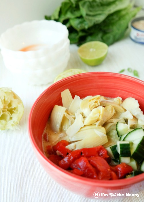 Adding artichokes hearts, roasted red peppers, and cucumbers into vinaigrette